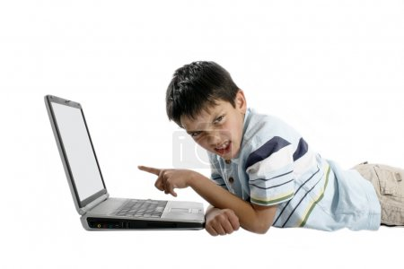 Frustrated young boy pointing at a laptop...