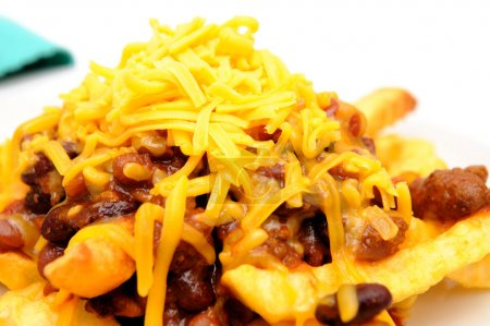 Photo for Melting cheddar cheese over the top of french fries covered in spicy chili with meat and beans - Royalty Free Image