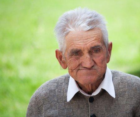 Photo pour Gros plan portrait d'un vieil agriculteur sur fond vert flou - image libre de droit
