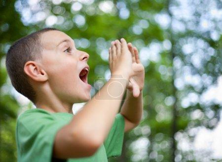 Foto de Cerrar el retrato de un niño gritando en el bosque - Imagen libre de derechos