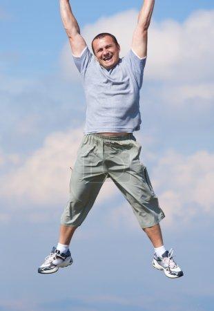 Photo pour Heureux jeune homme suspendu au bord supérieur de la photo, dans le ciel. Plan conceptuel - image libre de droit