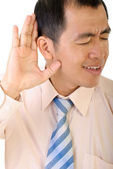 Businessman listen by gesture with his hand to ear