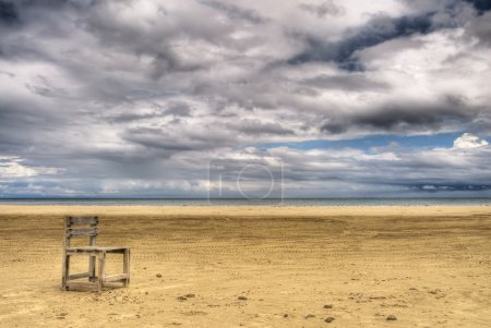 Photo for Alone scenic with single chair on yellow sand under white dramatic clouds in sky. - Royalty Free Image