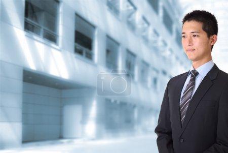Photo pour Asiatique jeune homme d'affaires debout et regardant devant des immeubles de bureaux . - image libre de droit