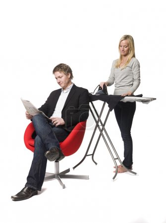 Photo pour Femme de repassage et l'homme lisant un journal - image libre de droit