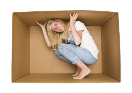 Photo for Young Woman inside a Cardboard Box isolated on white Background - Royalty Free Image