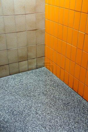 Photo pour Coin salle de bains public où se rencontrent trois revêtements différents, carreaux orange et beige avec un plancher de vinyle moucheté. Funky! - image libre de droit