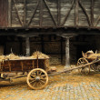 Wooden cart with dried hay in front of an old barn...