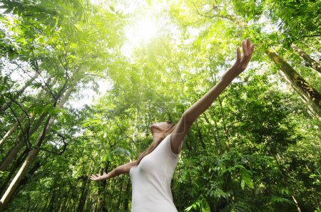 Photo for Young woman arms raised enjoying the fresh air in green forest - Royalty Free Image