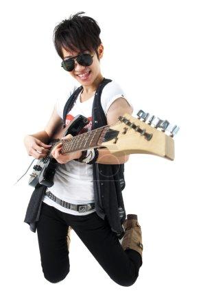Photo pour Rockstar punk tenant une guitare à genoux isolé en blanc - image libre de droit