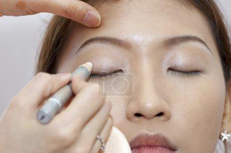 Photo pour Femme appliquant cosmétique avec applicateur. Traitement de maquillage . - image libre de droit
