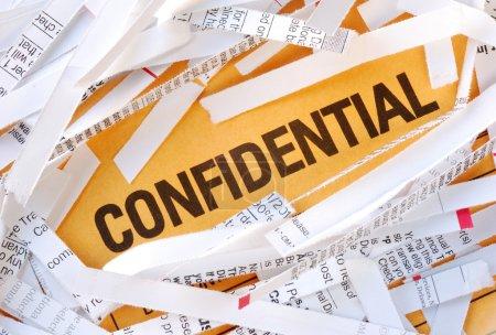 Photo pour Le mot confidentiel entouré des papiers déchiquetés - image libre de droit