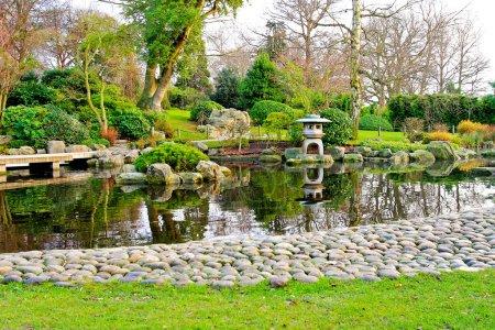 Photo pour Bienheureuse jardin japonais avec chemin de galets et lac - image libre de droit