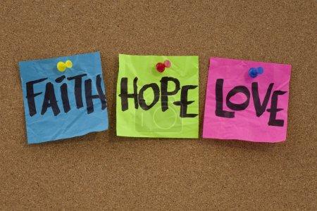 Photo pour Rappel spirituel ou concept métaphysique - foi, espérance et d'amour écrite à la main sur des notes colorées et affiché sur le babillard de Liège - image libre de droit