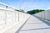 Long walking path in a modern white metal bridge