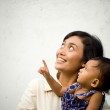 Asian ethnic mother and baby looking up and pointi...