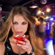 Girl with cocktail on dancing background