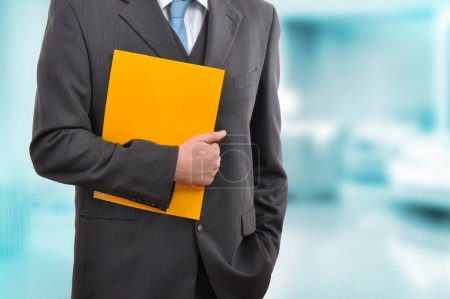 Photo for Businessman in gray suite holding a yellow folder - Royalty Free Image