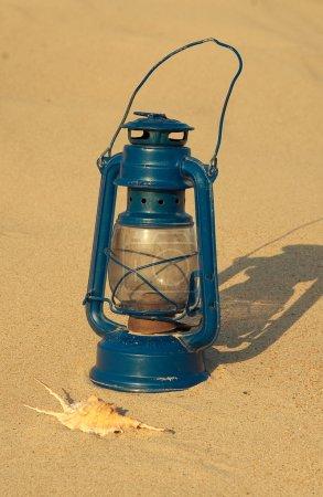 Old lamp on the sandy beach
