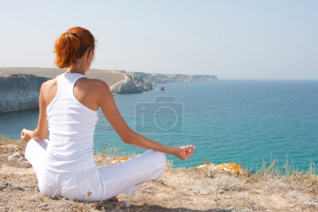 Photo for Woman in white meditating in mountains - Royalty Free Image