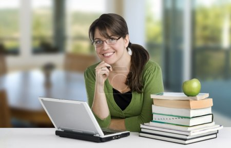 Young woman posing as a student or teacher with books, laptop, and apple, wearing glasses and green top