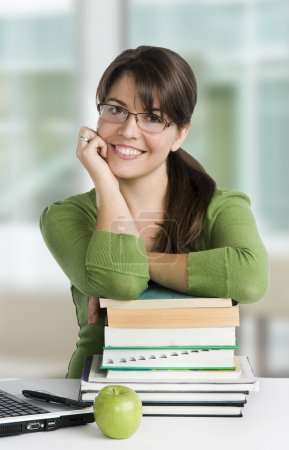 Photo for Young woman posing as a student or teacher with books, laptop, and apple, wearing glasses and green top - Royalty Free Image