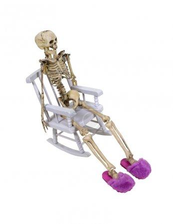 Photo pour Un squelette allongé dans une chaise berçante, porter des pantoufles floues roses - chemin d'accès inclus - image libre de droit
