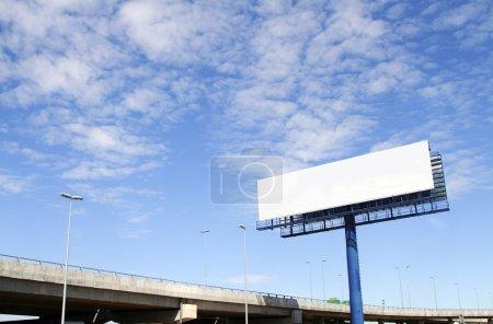 Photo pour Un panneau d'affichage vide avec une autoroute surélevée en arrière-plan - image libre de droit