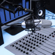 A mic in front of the control panel and screen in broadcasting studio