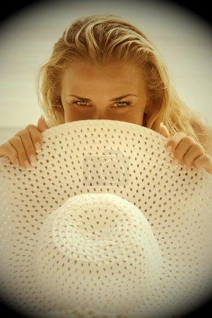 Foto de Belleza rubia con sombrero blanco en las manos en la playa - Imagen libre de derechos