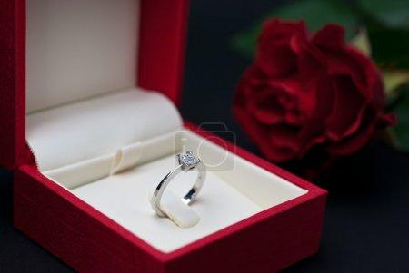 Photo pour Bague de fiançailles en diamant moderne en boîte à bijoux rouge sur fond noir (mise au point douce ) - image libre de droit