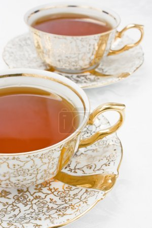 Photo for Two cup with tea from gold porcelain tea-set - Royalty Free Image