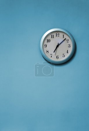 Photo for A blue and white clock on a blue wall - Royalty Free Image