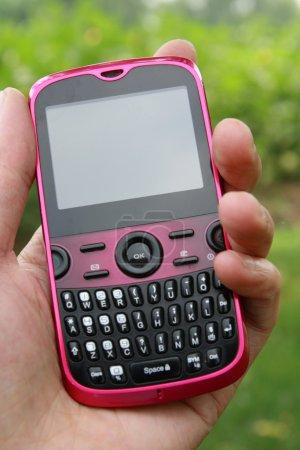 Photo pour Un rose téléphone portable dans la main avec écran blanc - image libre de droit