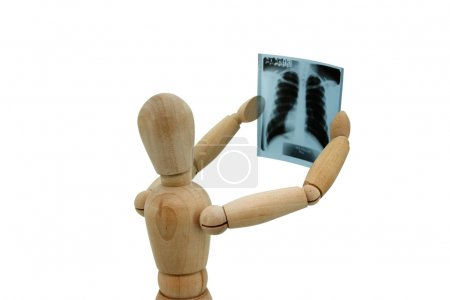 A wooden figurine looking at x-ray image