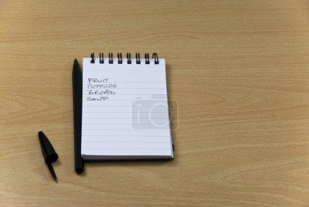 Photo pour Shopping List Bloc-notes avec stylo sur le plan de travail - image libre de droit