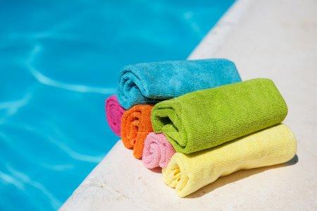 Photo pour Coloré serviettes roulés près de la piscine - image libre de droit