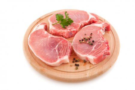 Fresh pork chops or cutlets with parsley on round ...