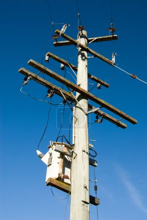 Photo pour Un poteau de bois supportant un transformateur et lignes électriques - image libre de droit