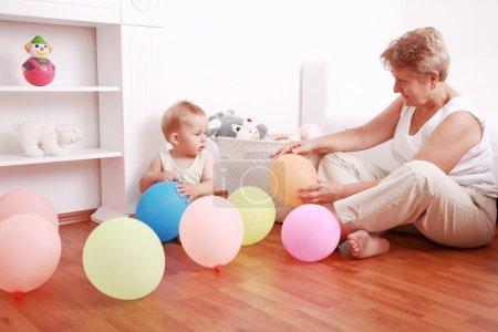 Photo pour Mignon petit garçon jouant avec sa grand-mère - image libre de droit