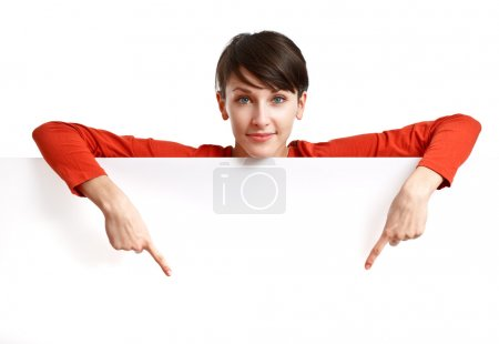 Photo for Beautiful girl behind an empty white board pointing her fingers down - Royalty Free Image