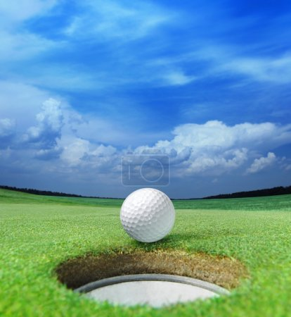 Photo for Golf ball on lip of cup of lovely beautiful golf course - Royalty Free Image