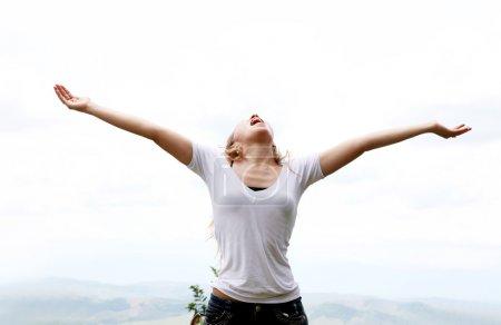 Photo pour Jeune femme aux bras tendus exprimant sa liberté - image libre de droit