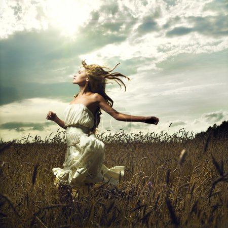 Photo for Portrait of romantic woman running across field - Royalty Free Image