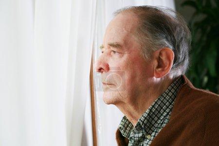 Photo pour Homme âgé regardant par la fenêtre avec une expression solitaire - image libre de droit