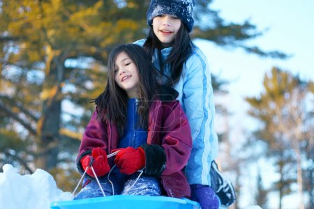 Two girls sledding