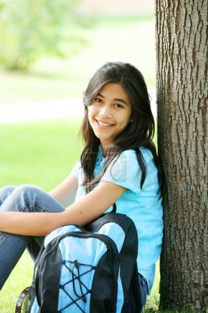 Young teen girl sitting against tree with backpack