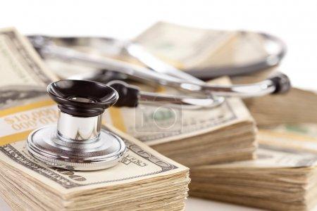Photo pour Stéthoscope posé sur des piles de billets de cent dollars avec une profondeur de champ étroite . - image libre de droit