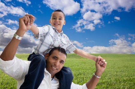 Foto de Feliz hispano padre e hijo en el campo de hierba, las nubes y cielo azul - Imagen libre de derechos