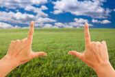 Hands Making a Frame Over Grass Field